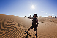 Africa, Namibia, Namib Desert, Namib Naukluft National Park, Mature man drinking water from water bottle - FOF002401