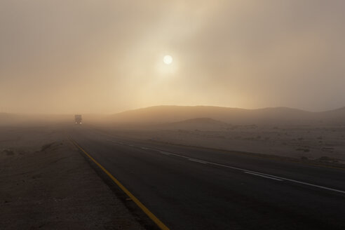 Africa, Namibia, Namib Desert, Swakopmund, View of vehicle on foggy road at dawn - FOF002418