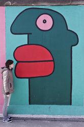 Germany, Berlin, Young woman standing near berlin wall - WVF000053
