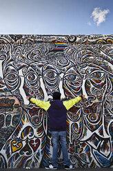 Germany, Berlin, Teenage boy standing against berlin wall - WVF000056