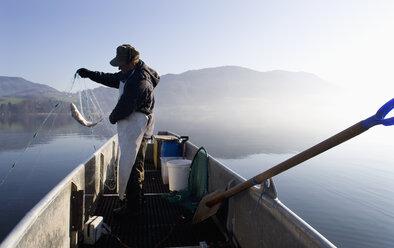 Austria, Mondsee, Fisherman caught a fish in fishing net - WWF001682