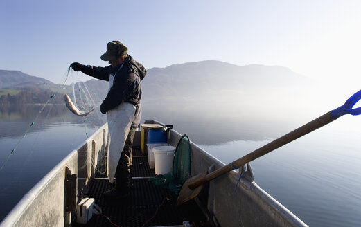 Austria, Mondsee, Fisherman caught a fish in fishing net - WWF001682