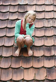 Austria, Mondsee, Girl (12-13 Years) sitting on roof top, portrait - WWF001633