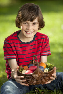 Germany, Boy (10-11 Years) smiling with easter egg basket, portrait - MAEF002514
