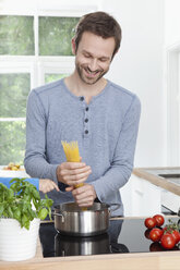 Germany, Bavaria, Munich, Man cooking spaghetti in kitchen - RBF000367