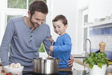 Germany, Bavaria, Munich, Father and son (2-3 Years) preparing meal in kitchen - RBF000373