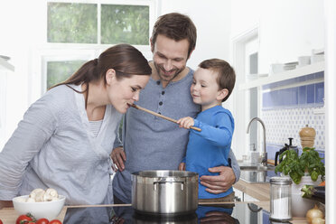 Germany, Bavaria, Munich, Son (2-3 Years) feeding mother, family in the kitchen - RBF000378