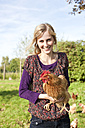 Germany, Saxony, Young woman with hens, portrait, smiling - MBF001038