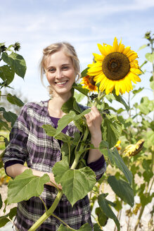 Germany, Saxony, Young woman with sunflower, smiling - MBF001124