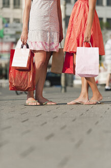 Germany, Munich, Karlsplatz, Young women waiting on footpath with shopping bags - RNF000455