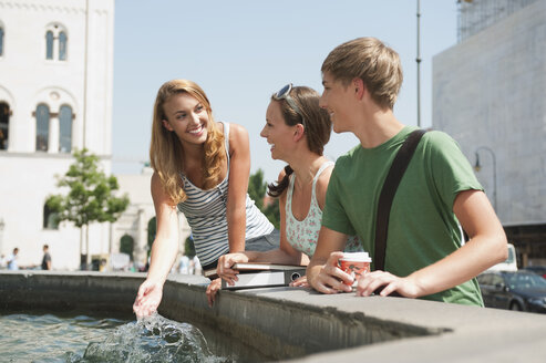 Germany, Munich, Young man and young women at fountain - RNF000389