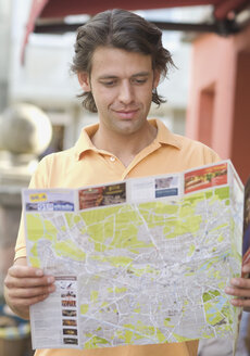 Germany, Nuremberg, Young man looking at map - WBF000501