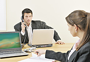 Businesswoman and man working in office - WBF000509