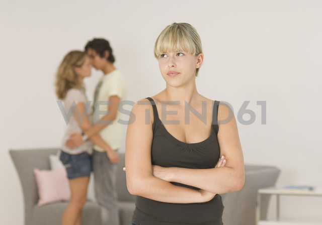 Young woman looking away with couple in background - WBF000535