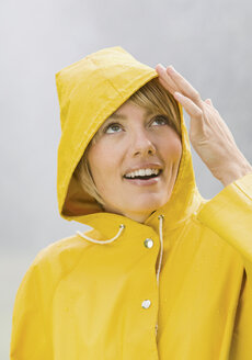 Woman in yellow rain coat looking up and smiling - WBF000781