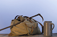 Walking stick, beer mug and backpack on table - ASF004252