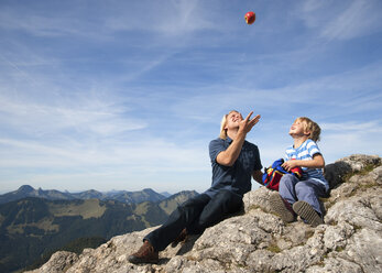 Germany, Bavaria, Father and son (4-5 Years) playing with ball on mountain summit - HSIF000018