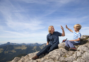 Germany, Bavaria, Father and son (4-5 Years) sitting on mountain summit - HSIF000015