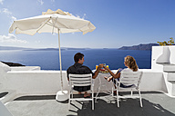 Greece, Cyclades,Thira, Santorini, Oia, Mature couple relaxing with blue sea in background - FO002888