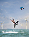 Croatia, Zadar, Kitesurfer jumping in front of wind turbine - HSIF000061