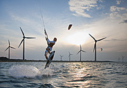 Croatia, Zadar, Kitesurfer jumping in front of wind turbine - HSIF000060