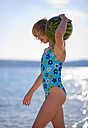 Croatia, Zadar, Girl carrying watermelon at beach - HSIF000028
