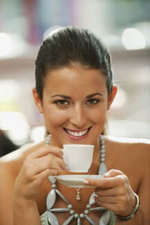 Germany, Munich, Young woman drinking coffee in cafe, smiling, portrait - RNF000512