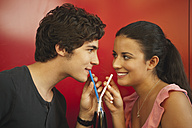 Germany, Munich, Young couple sharing a drink with straws in cafe - RNF000494