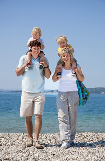 Croatia, Zadar, Parents carrying children on shoulder at beach - HSIF000095