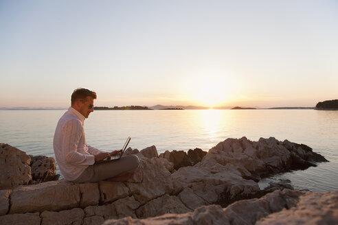 Croatia, Zadar, Young man using laptop on beach - HSIF000100