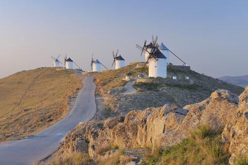 Spain, Toledo Province, Castile-La Mancha, Row of windmills with rural road at sunrise - RUEF000612