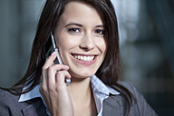 Germany, Bavaria, Business woman on the phone, smiling, portrait - MAEF002703