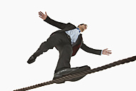 Businessman balancing on tightrope - RBF000464