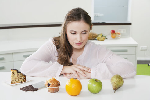 Germany, Cologne, Young woman is confused between fruits and sweets - PDF000081