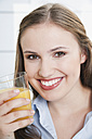 Germany, Cologne, Young woman with glass of juice, smiling, portrait - PDF000116