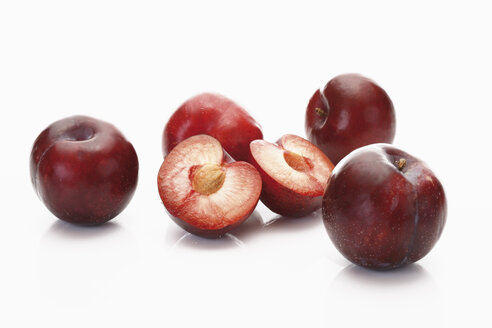 Red plums on white background, close up - CSF014137