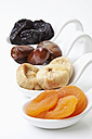 Variety of dried fruits in spoon on white background - MAEF002823