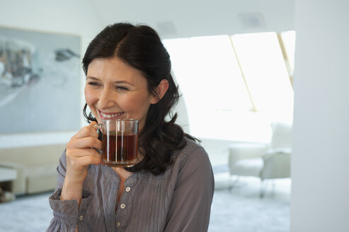 Germany, Munich, Mature woman holding cup, smiling, portrait - NHF001314