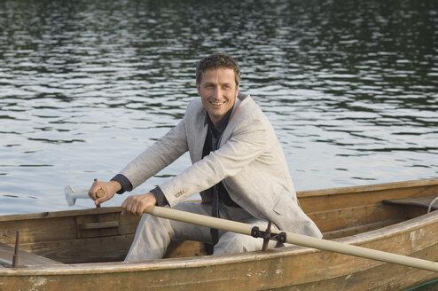 Germany, Bavaria, Wesslinger See, Business man rowing boat in lake after work - CRF002011