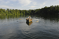 Germany, Bavaria, Wesslinger See, Business man rowing boat in lake after work - CRF002012
