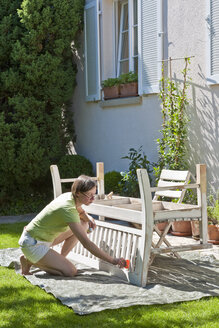 Germany, Stuttgart, woman painting bench in garden - WDF000868