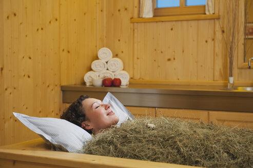 Italy, South Tyrol, Woman having hay bath in hotel urthaler - WESTF015800