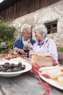 Italy, South Tyrol, Mature couple having their snacks at mountain hut - WESTF016012