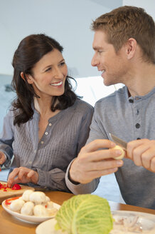 Germany, Munich, Man and woman cooking in kitchen, smiling - NHF001283