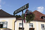 Austria, Lower Austria, Wachau, Waldviertel, Weissenkirchen, Text Heuriger on arrow sign with buildings - SIEF000237
