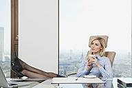 Germany, Frankfurt, Business woman sitting in office with coffee mug - SKF000429