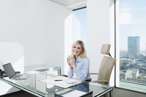 Germany, Frankfurt, Business woman sitting in office with coffee mug - SKF000432