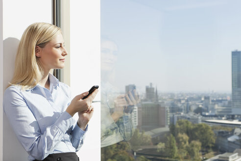 Germany, Frankfurt, Business woman with cell phone - SKF000444