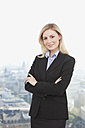 Germany, Frankfurt, Business woman smiling with arms crossed, portrait - SKF000447