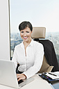 Germany, Frankfurt, Business woman using laptop, smiling, portrait - SKF000456